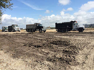 Dump trucks at the future ConRAC site
