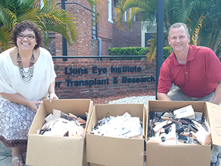 Lion's Eye Institute Foundation  Development Coordination Angela Pottinger and TPA Manager of Administration Mitch Thrower pose with just a few of the donated boxes of eyeglasses